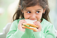 Little girl eating sandwich at home