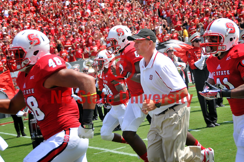 Football coach Dave Doeren runs out onto the field at Carter Finley Stadium for his first game as the Wolfpack's head coach.