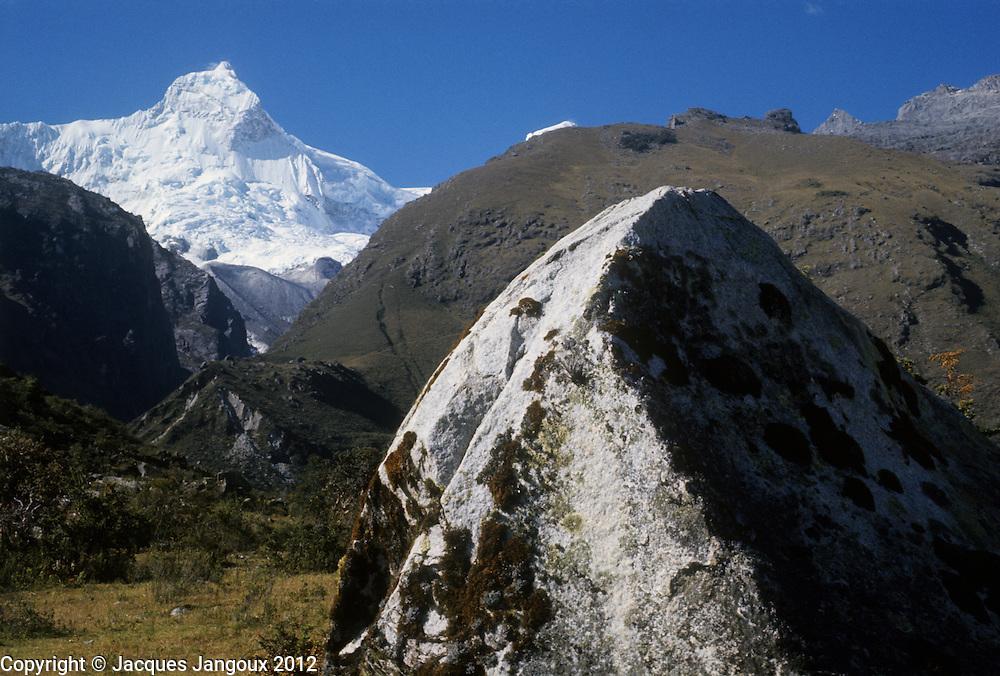 Peru, Andes Montain Range - Cordillera de los Andes, Cordillera Blanca mountain range, snow-covered Mount Huandoy (6395 m), with boulder in foreground.