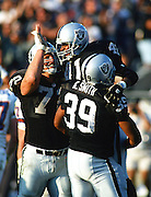 Los Angeles Raiders running back Napoleon McCallum (41) jumps in the air as he celebrates with Raiders center Don Mosebar (72) and Raiders tight end Kevin Smith (39) during the 1994 NFL AFC Wild Card playoff football game against the Denver Broncos on Jan. 9, 1994 in Los Angeles. The Raiders won the game 42-24. (©Paul Anthony Spinelli)