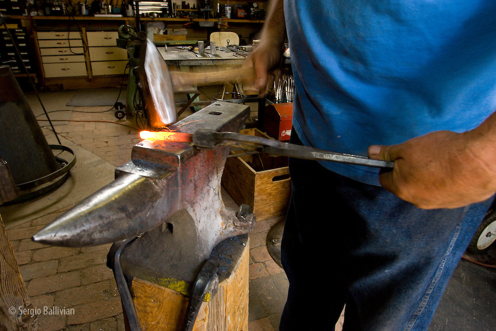 Blacksmith working raw iron in his furnace in Santa Fe, New Mexico