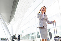 Young attractive businesswoman talking on smartphone while walking with her suitcase in airport