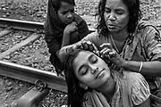 Mother and daughter in a slum near their home in Bangladesh. She is having her head and hair cleaned by her mother.