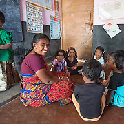 CAPTION: Jayamala keeps an eye on Madhushree while leading a game at her anganwadi (pre-school). Through the Chamkol programme's Early Years' Clubs, anganwadi workers like Jayamala will play more of a role in the lives of the youngest children with special needs, like Madhushree, who has autism. LOCATION: Masagapura (village), Kasaba (hobli), Chamrajnagar (district), Karnataka (state), India. INDIVIDUAL(S) PHOTOGRAPHED: From left to right (visible faces only): Madhushree, Jayamala, Chamdama M., Radhika B., Chamdama M. and Aishwarya S.