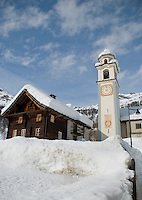 Ticino, Southern Switzerland. Bosco Gurin. Church tower and traditional chalet in the snow.