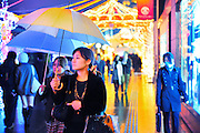 Christmas time in Shinjuku, Tokyo Japan. Busy shoppers enjoying the Xmas illumination in the rain.