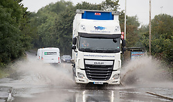A lorry goes through a large puddle near Colnbrook, Berkshire as a yellow weather warning for rain has been issued for parts of the UK.