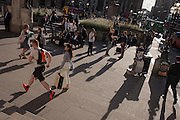 A jogger runs through Bank Triangle in the City of London, while a rush-hour crowd of commuters gather to meet and sit in late summer sunshine.