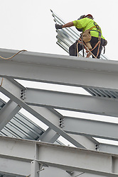 Steel Worker grasping and positioning a roof panel. During Steel Erection at the Central Connecticut State University New Academic Building Construction.
