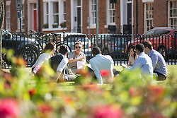 © Licensed to London News Pictures. 27/06/2015. Leeds .UK. Picture shows office workers having a meeting outside in Park Square in Leeds. Britain is set to sizzle in temperatures of up to 34C (93F) today, with forecasters predicting the hottest day for several years. A tropical air mass moving from North Africa, Spain and Portugal means that we could be hotter than Rio de Janeiro.Photo credit : Andrew McCaren/LNP