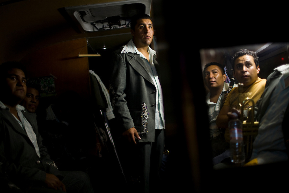 Members of a Nortena band sit in their tour bus after giving a show in Mexico City. Many Nortena groups sing corridos, or songs that tell a story.  Some of these are narco-corridos, songs that tell the stories of famous drug dealers.  There has been a wave of killings of musicians that sing narco corridos.