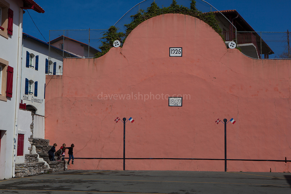 Kids jumping from a wall in pelota court in the  town of Bidart, Biarrtiz, Basque country, France