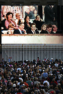 Crowds outside Buckingham Palace watch a broadcast of a rock concert held in Buckingham Palace's grounds to celebrate Queen Elizabeth II's Golden Jubilee. Princes Charles, William and Harry are seen on screen laughing at a comedian's joke. Celebrations took place across the United Kingdom with the centrepiece a parade and fireworks at Buckingham Palace, the Queen's London residency. Queen Elizabeth ascended to the British throne in 1952 upon the death of her father, King George VI.