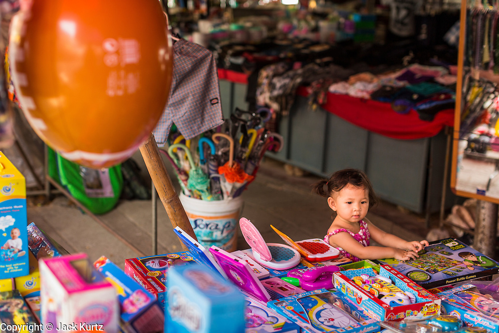 24 APRIL 2014 - CHIANG SAEN, CHIANG RAI, THAILAND:  A Thai child looks at cheap imported toys from China in a market on the Mekong riverfront promenade in Chiang Saen, Chiang Rai province, Thailand. Chinese businesses play an increasingly important role in the Chiang Rai economy. Consumer goods made in China are shipped to Thailand while agricultural products made in Thailand are shipped to China. Large Chinese cargo boats ply the Mekong River as far south as Chiang Saen in the dry season and Chiang Khong when river levels go up in the rainy season.    PHOTO BY JACK KURTZ