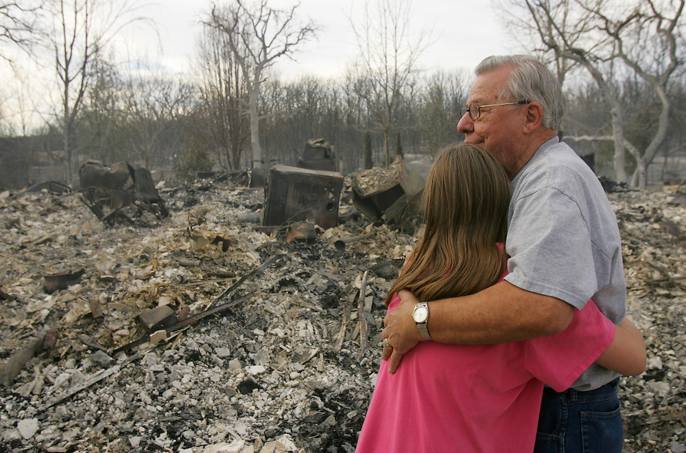 © 2005 Alex Jones www.alexjonesphoto.com..Richard Chaffin consoles family friend Lakeney Walker, age 10, outside the remains of his burned house on Wednesday, December 28, 2005 in Cross Plains, Texas.  The town was heavily damaged by an uncontrolled grass fire on Tuesday, one of many in the state.