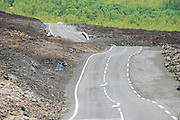 Curved asphalt road over volcanic lava, Reunion island, France.