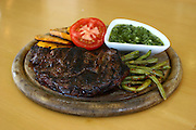 Grilled steak meal on wooden platter with vegetables