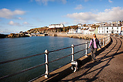 Middle-aged woman and dog walking next to Portpatrick harbour Southern Upland Way