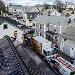 Solar panels being installed on a roof in Lowell, Massachusetts.