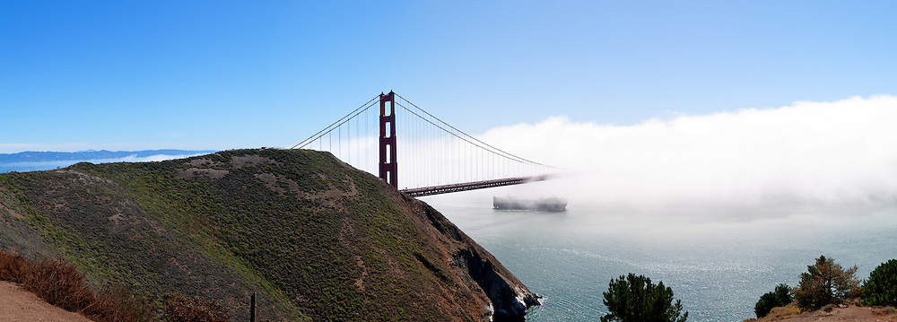 Panoramic shot of Golden Gate Bridge on a sunny day partially obscured by fog with a ship heading out to sea