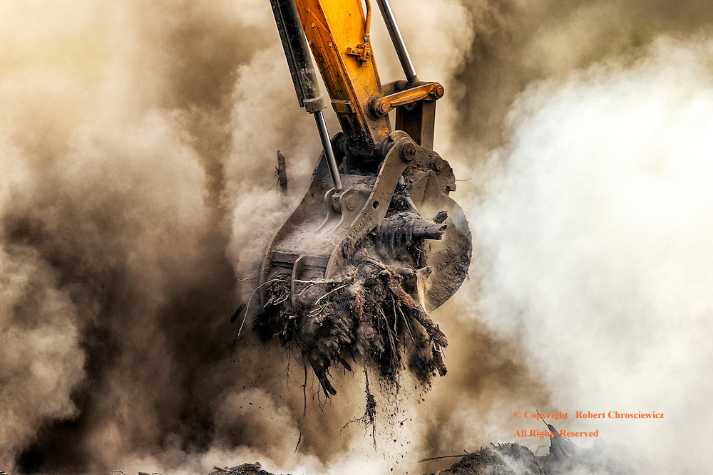 Grasped Within: Grasping its fill, an excavators' bucket transports its load through the waves of smoke that obscures the work site, Aldergrove British Columbia, Canada.