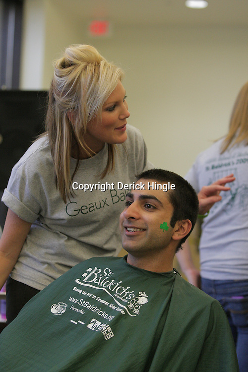 12 March 2009: Emily Jordan, 24 a hematology and oncology nurse at Children's Hospital gets her head shaved by Kiel Whitener (R) of Salon Stefano during the annual St. Baldrick's children's cancer charity fund raiser held at Parasol's Bar in the Irish Channel of New Orleans, Louisiana.