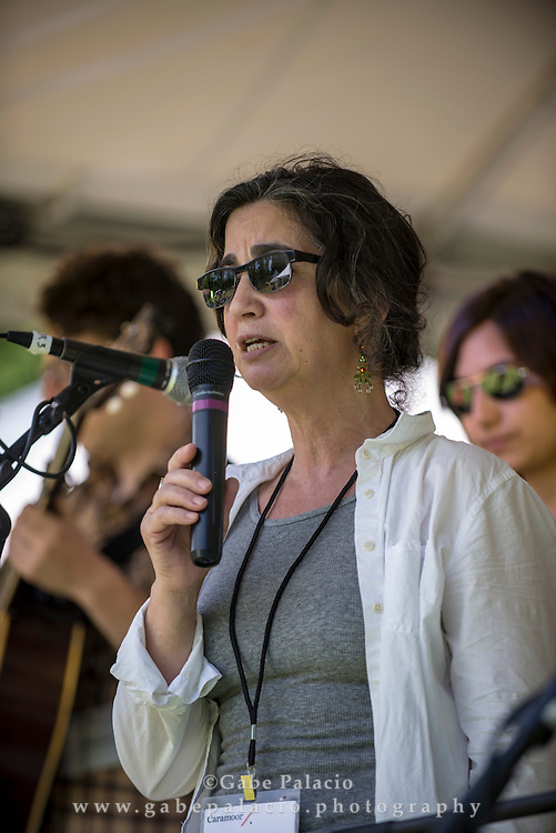 Maggi Landau, Artistic Director for Roots Music at Caramoor, makes introductions at  the Friends Field set at the American Roots Music Festival at Caramoor in Katonah New York on June 28, 2014. <br /> (photo by Gabe Palacio)