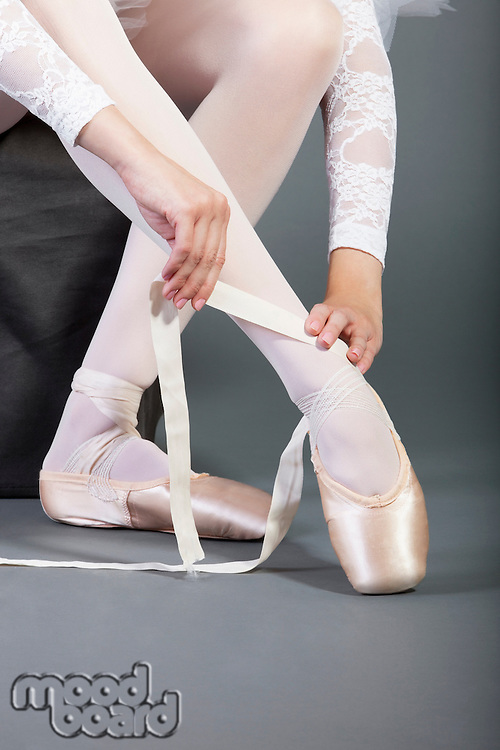 Low section of female ballet dancer tying pointe shoes