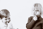 Brother and sister playing and amused by magnifying glass