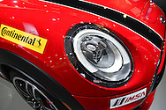 A red MINI Cooper has a Continental and an IMSA sticker at the New York International Auto Show 2016, at the Jacob Javits Center. The MINI John Cooper Works racing team has 3 cars in the 2016 Continental Tire SportsCar Challenge, and IMSA is the International Motor Sports Association. This was Press Preview Day one of NYIAS, and the Trade Show will be open to the public for ten days, March 25th through April 3rd.