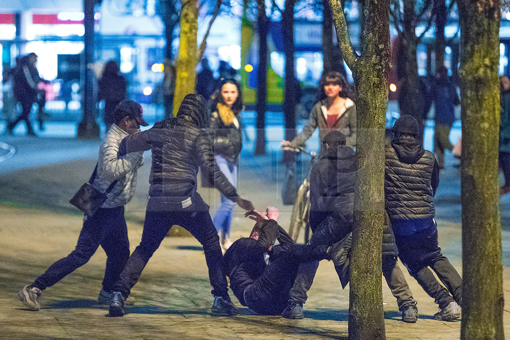 © Licensed to London News Pictures . 07/04/2017 . Manchester , UK . 2nd in a sequence . Five youths on one as a fight breaks out in Piccadilly Gardens . Greater Manchester Police have authorised dispersal powers and say they will ban people from the city centre for 48 hours , this evening (7th April 2017) , in order to tackle alcohol and spice abuse . Photo credit : Joel Goodman/LNP