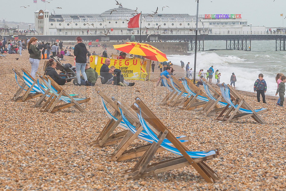 © Licensed to London News Pictures. 17/08/2019. Brighton, UK. Deck chairs stand unused on the beach in Brighton and Hove as grey clouds and colder weather is hitting the seaside resort. Photo credit: Hugo Michiels/LNP