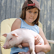 Nervous girl 8-10 years sits in chair holding heavy piglet