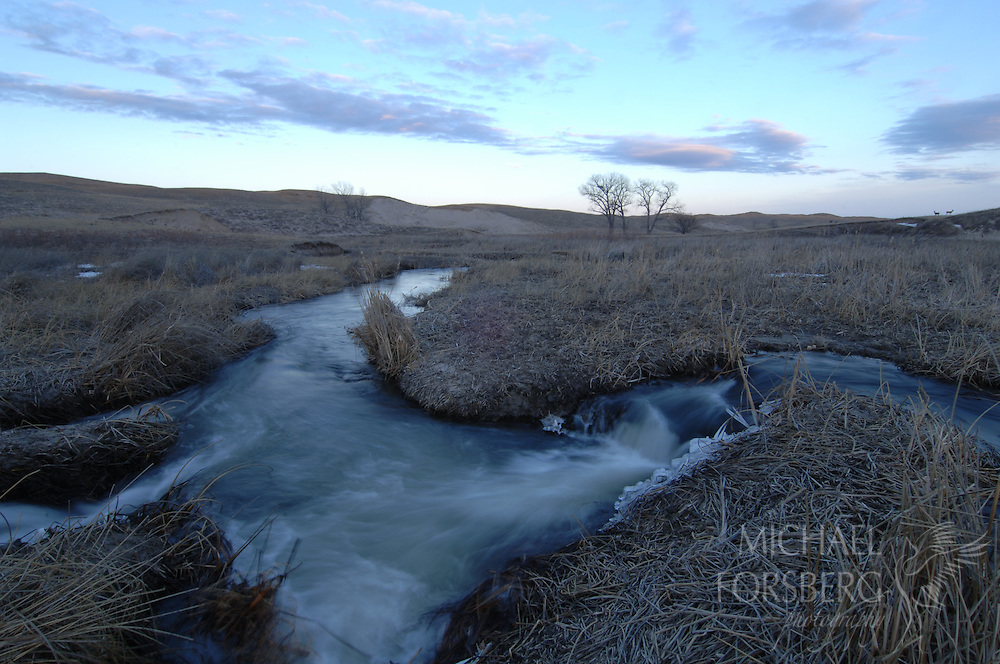 Nebraska Sandhills. .Small waterfalls along Blue Creek in winter with Mule deer on horizon..Blue Creek stays open even in the deepest cold of winter, fed by powerful underground springs from the Ogallala aquifer below.