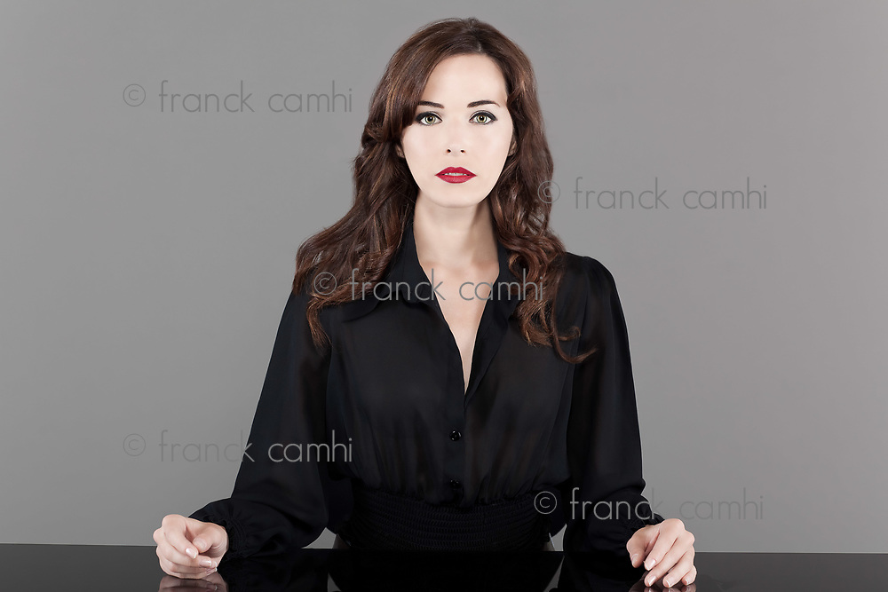 Portrait of a beautiful brunette woman in black casual sitting at table isolated on gray background