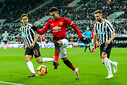 Isaac Hayden (#14) of Newcastle United controls the ball in the penalty area under pressure from Paul Dummett (#3) of Newcastle United and Yoshinori Muto (#13) of Newcastle United during the Premier League match between Newcastle United and Manchester United at St. James's Park, Newcastle, England on 2 January 2019.