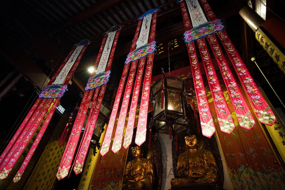 Golden Buddhas and silk banners in the Grand Hall of Magnificence of the Jade Buddha Temple, Shanghai, China