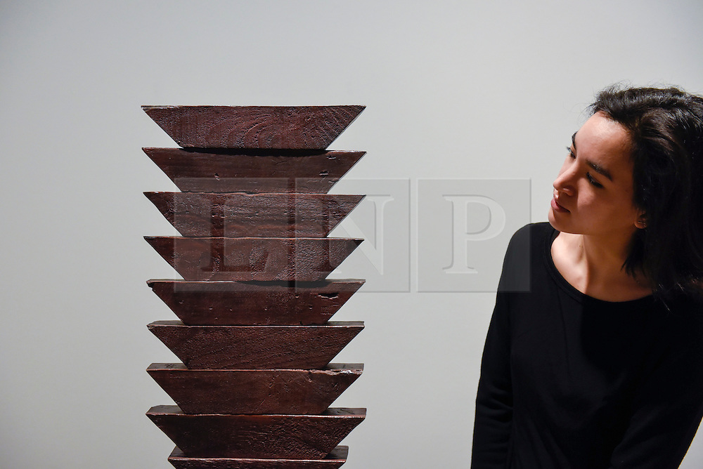 """© Licensed to London News Pictures. 17/02/2017. London, UK.   A staff member views """"Untitled (The Wedges)"""" by Louise Bourgeois, at a preview of """"Traumata: Bourgeois/Kusama"""".  The joint exhibition is dedicated to the work of Louise Bourgeois and Yayoi Kusama, and takes place at Sotheby's S/2 Gallery 23 February to 13 April. Photo credit : Stephen Chung/LNP"""