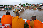Phnom Penh, Cambodia. Sunset cruise to the confluence of Tonle Sap and Mekong river.<br /> Buddhist monks looking at Areyksat village.