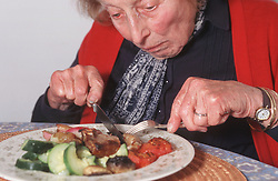 Elderly woman eating meal,