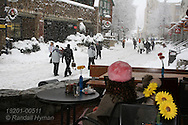 Young woman sits on cozy cafe porch watching crowds pass in ski resort village at Whistler, British Columbia, Canada