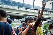 """01 JUNE 2014 - BANGKOK, THAILAND: A man holds up a three fingered salute during a protest against the Thai military coup at Terminal 21 a popular shopping mall in Bangkok. The salute is from the movie """"The Hunger Games"""" and symbolizes it admiration, thanks and good-bye to a loved one. In this case, the loved one is reportedly Thai democracy. The Thai army seized power in a coup that unseated a democratically elected government on May 22. Since then there have been sporadic protests against the coup. The protests Sunday were the largest in several days and seemed to be spontaneous """"flash mobs"""" that appeared at shopping centers in Bangkok and then broke up when soldiers arrived. Protest against the coup is illegal and the junta has threatened to arrest anyone who protests the coup. There was a massive security operation in Bangkok Sunday that shut down several shopping areas to prevent the protests but protestors went to malls that had no military presence.    PHOTO BY JACK KURTZ"""