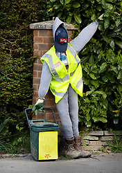 © Licensed to London News Pictures. 27/04/2020. Capel, UK. A scarecrow tribute to a refuse collector stands on the drive of a house in the Surrey village of Capel. Residents of the village have resurrected their summer tradition of scarecrows in tribute to NHS medical staff and other key workers. Up to 30 of the life size home made doll like characters can be seen in front gardens throughout the village. The public have been told they can only leave their homes when absolutely essential, in an attempt to fight the spread of coronavirus COVID-19 disease. Photo credit: Peter Macdiarmid/LNP