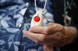 Elderly woman holding a panic buzzer,