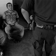A U.S. Customs and Border Patrol Officer questions Mexican men during a secondary search in the southbound lanes in Laredo, Teas before they head back to Mexico..(Credit Image: © Louie Palu/ZUMA Press).June 2012