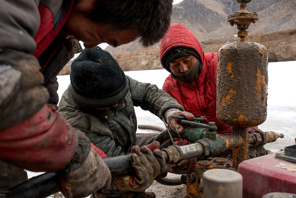 Workers repair a piece of malfunctioning machinery on the frozen crust of the Mekong river. The team is taking earth samples from the river bed in preparation for the construction of a new bridge over the Mekong in Zado, Tibet (Qinghai, China).