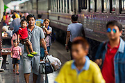 16 APRIL 2014 - BANGKOK, THAILAND:  Passengers arriving in Bangkok on a train from Chiang Mai walk through Hua Lamphong Railway Station in Bangkok. Thai highways, trains and buses were packed Wednesday as Thais started returning home after the long Songkran break. Songkran is normally three days long but this year many Thais had at least an extra day off because the holiday started on Sunday, so many Thais started traveling on Friday of last week.   PHOTO BY JACK KURTZ