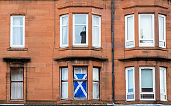 Typical view of tenement apartment building with Scottish flag in window in Govanhill district of Glasgow, Scotland, United Kingdom