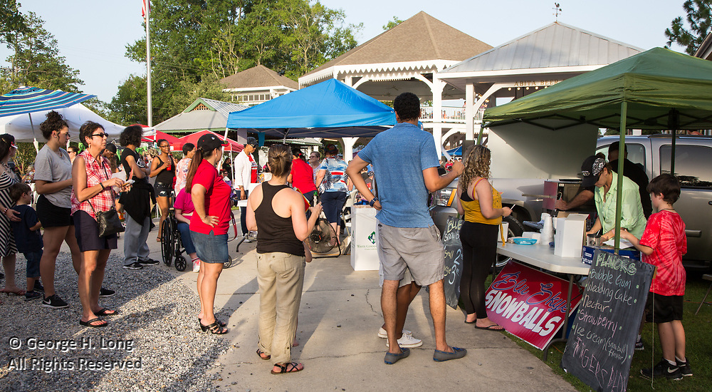Blu Skye Art & Coffee sells snowballs from their tent to people gathering in Abita Springs Park before fireworks on July 2, 2017