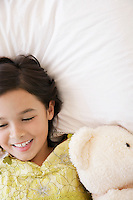Girl lying on bed with teddy bear smiling head and shoulders